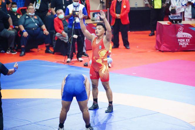Lulut Gilang Saputra mengangkat tangan usai mengalahkan  pegulat papua Sumurung  Siregar di partai final kekas 87 kg