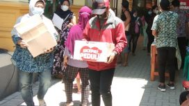 Warga membawa pulang paket sembako usai mengikuti vaksinasi di Balai Desa Sawocangkring.